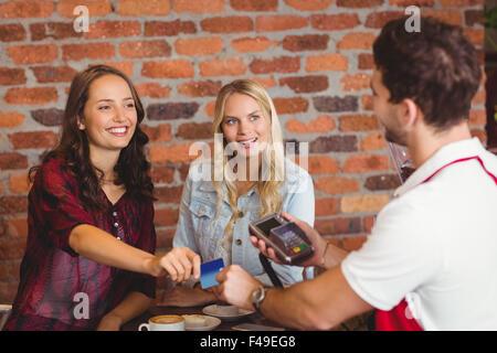 Pretty friends handing a credit card - Stock Photo