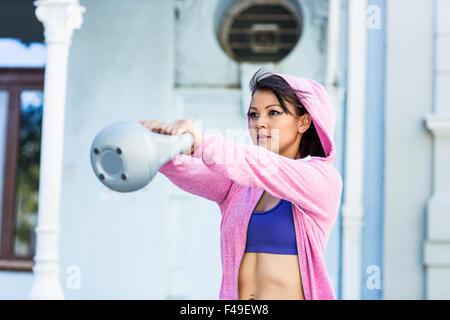 Athletic woman swinging kettlebell - Stock Photo