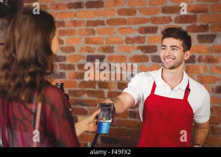 Smiling waiter handing a pin terminal - Stock Photo