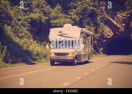Vintage style image of recreational vehicle camper driving on highway