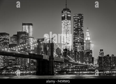 Black & White cityscape by night. View of Brooklyn Bridge, Lower Manhattan and  Financial District's skyscrapers, - Stock Photo