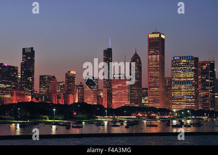 A portion of the Chicago skyline provides a foreground to a colorful sky as sunset turns to dusk in the city. Chicago, - Stock Photo