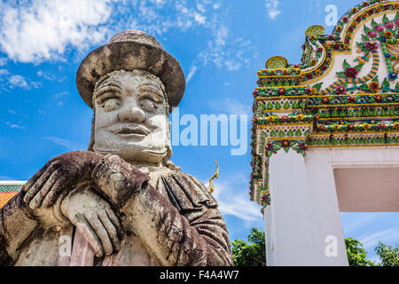 Thailand, Bangkok, Wat Po, warrier statue with top hat guarding a gate to the buddhist temple - Stock Photo