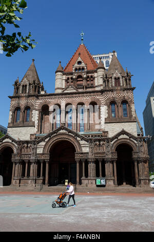 Female pushing child's buggy in front of Trinity Church in Copley Square in  the City of Boston Richardsonian Romanesque - Stock Photo
