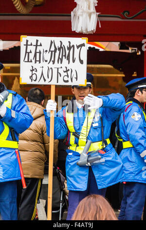 Ikuta shrine in Kobe, during New Year. Blue coated elderly Japanese security men with hand held sign and bullhorn, - Stock Photo