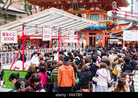 Ikuta shrine, Kobe. New Year. Crowds filling the shrine buying fortune papers, omikuji, from Miko, shrine maidens - Stock Photo
