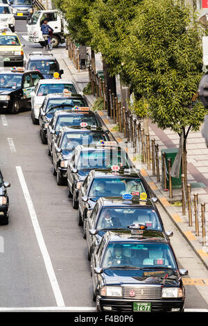 Japan, Osaka, Umeda. Overhead view looking down along at a lone line of Japanese taxis waiting on a main street. - Stock Photo