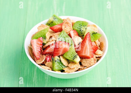 Corn flakes with fresh strawberry and kiwi slices in bowl on green table - Stock Photo