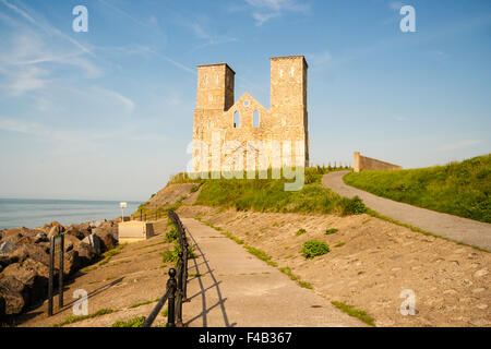 Kent coast, England. Reculver, Remains of the 12th century St Mary's church and its twin towers on the seawall promenade. - Stock Photo