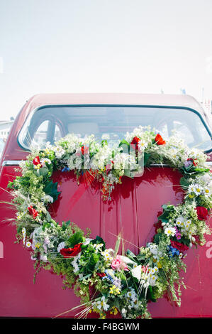 Bouquet on a red wedding car - Stock Photo