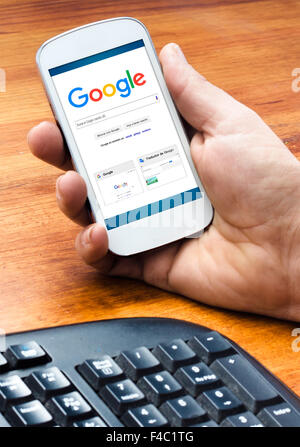 Barcelona, Spain- September 4, 2015: Male hand holding on smartphone with Google Web Search homepage on the screen - Stock Photo