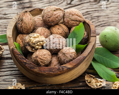 Walnuts in the wooden bowl on the table. - Stock Photo