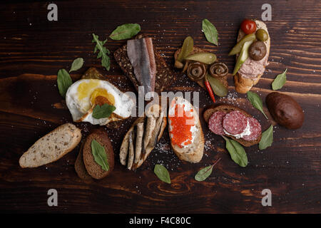 Variety of open sandwiches from wholegrain baguette and rye bread with different toppings over dark wooden backdrop. - Stock Photo