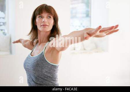 Portrait of mature woman stretching her arms and looking away at gym. Beautiful woman performing yoga in warrior - Stock Photo