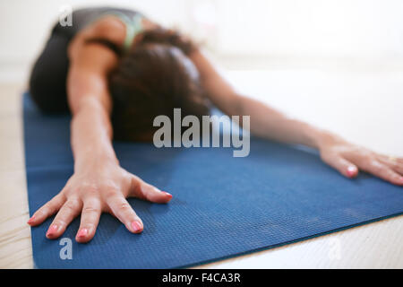 Woman stretching forward, performing a yoga pose on exercise mat. Fitness female performing balasana yoga at gym, - Stock Photo