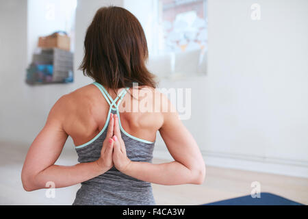 Rear view of fitness woman doing yoga  in reverse prayer pose. Pashchima Namaskarasana performed by a female at - Stock Photo