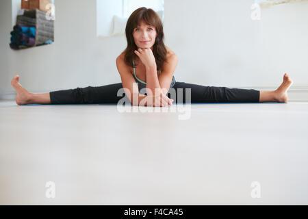 Portrait of flexible woman doing Upavistha Konasana exercise. Female yoga instructor practices yoga at gym. - Stock Photo