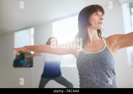 Shot of fitness woman doing yoga. Women exercising at yoga class. Virabhadrasana pose. - Stock Photo