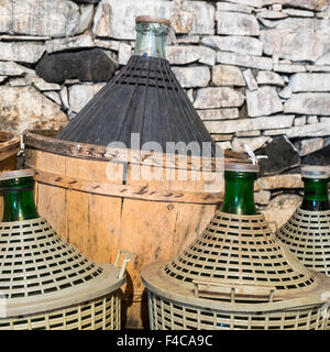 Demijohns of wine in a stone cellar. - Stock Photo
