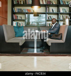 Shot of young african businessman sitting alone at coffee shop working on his laptop. Waiting for client for a meeting. - Stock Photo