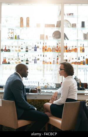 Portrait of young business people sitting together at cafe. Business man and woman meeting at cafe after work. - Stock Photo