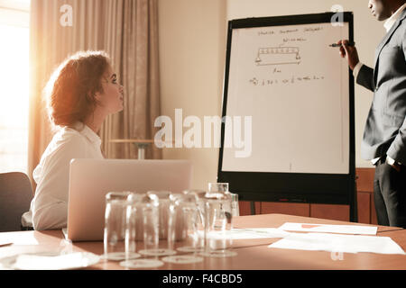 Portrait of an man sharing some of his thoughts on a flip board. Businessman explaining something to a colleague - Stock Photo