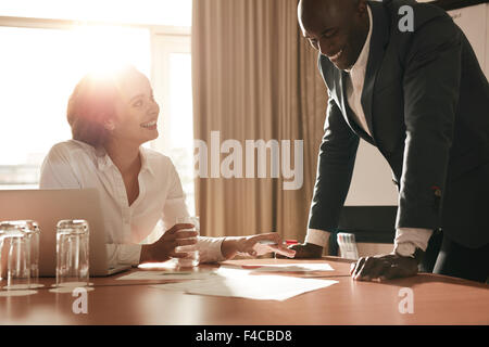 Two young business people meeting in conference room and working on new projects. Happy coworkers discussing new - Stock Photo