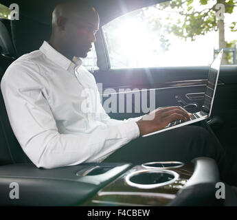Shot of young african businessman working on laptop inside a car. Business associate travelling to work in a car. - Stock Photo