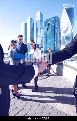 Business handshake, the deal Is finalized by group of people outside - Stock Photo