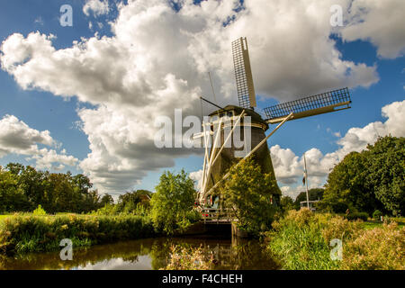 Traditional Dutch windmill on canal - Stock Photo