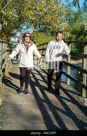 Couple walking over a wooden bridge Salisbury Wiltshire - Stock Photo