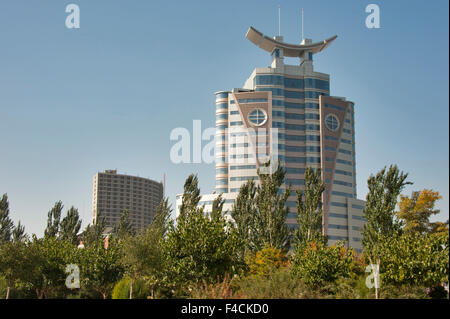 China, Ningxia, Yinchuan. One of the architecturally-dramatic Yinchuan office buildings towers above the trees lining - Stock Photo