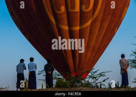 Asian Men standing in front of hot air balloon over Bagan - Stock Photo