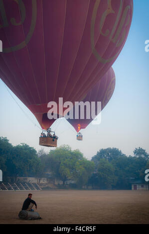 Asian Man sitting in front of two hot air balloons - Stock Photo