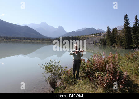 Man playing a viola at a  lake with mountainous  background - Stock Photo