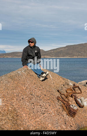 Canada, Nunavut, Kekerten Island. Kekerten Historic Park preserves whalers artifacts. Inuit guide and rusted whaling - Stock Photo