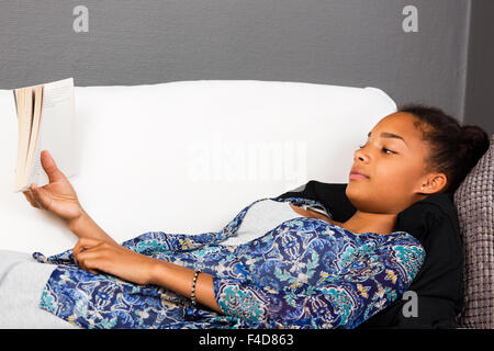 Girl laying in a couch reading a book. - Stock Photo