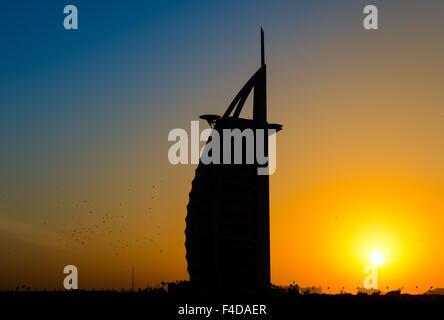 Silhouette of Hotel Burj Al Arab, Dubai, in sunset - Stock Photo