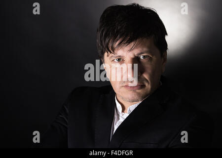 Handsome man in his 40's looking in the camera with a serious attitude. Wearing white shirt and a black jacket. - Stock Photo