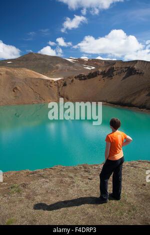Visitor admiring Viti crater, Krafla volcanic area, Myvatn, Nordhurland Eystra, Iceland. - Stock Photo