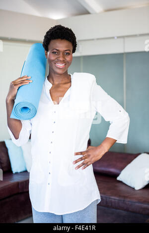 Portrait of happy pregnant woman holding exercise mat - Stock Photo