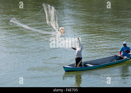 Guatemala, Izabal, Rio Dulce (Sweet Water River) near Livingston. Traditional fishermen in wooden boat tossing net - Stock Photo