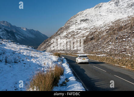 Llanberis Pass A4086 road with car passing through shot in winter wioth snow on mountains Snowdonia NP Gwynedd North - Stock Photo