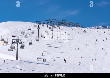 Skiers and double chairlift in Alpine ski resort in Solden in Otztal Alps, Tirol, Austria - Stock Photo