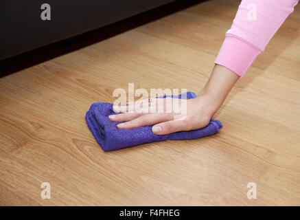 woman's hand cleaning the wooden floor with a blue floorcloth closeup - Stock Photo