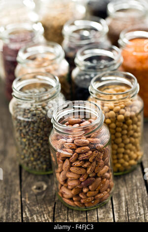 various dried legumes in jars on old table - Stock Photo