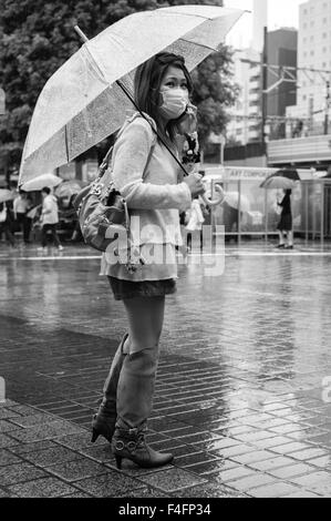 Woman wearing mask and carrying umbrella stands in the rain at the beginning of autumn in Shibuya, Tokyo - Stock Photo