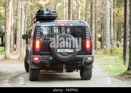 Saint-Petersburg, Russia - October 11, 2015: Black Hummer H2 vehicle goes on dirty country road in Russian forest, - Stock Photo