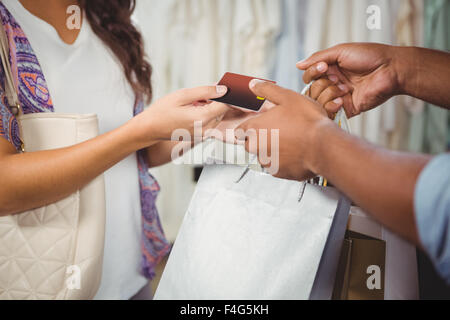 Man and woman exchanging credit card and bags - Stock Photo