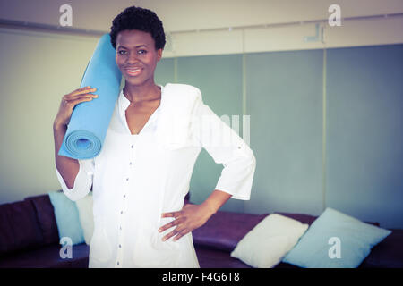 Portrait of pregnant woman holding exercise mat - Stock Photo